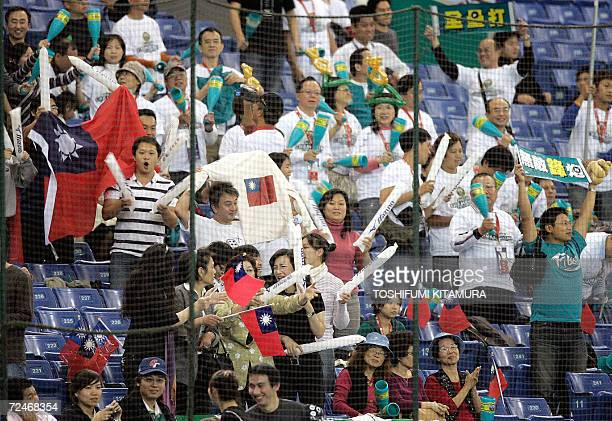 Taiwanese baseball fans celebrate La New Bears slugger Chin-Feng Chen's second homerun during the 8th inning of the match against China Stars in the...
