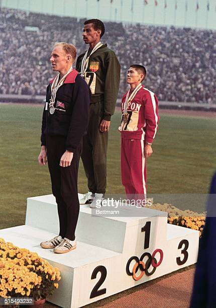the three winners of the marathon on platform after medal ceremony Heatley of Great Britain at left Abebe of Ethipia in center who placed third