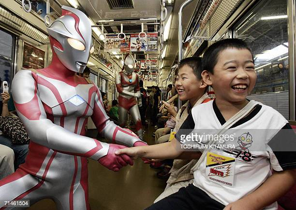 Ultra-hero, Ultraman Mebius shakes hands with young fans during a press preview inside a train in Tokyo, 17 July 2006. Ultra. The event was held to...