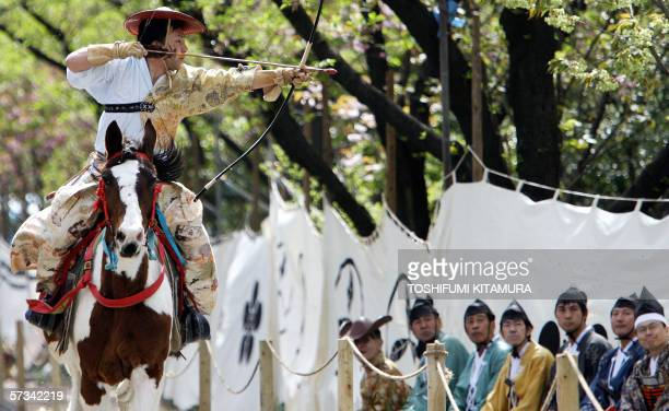 Wearing a hunting outfit of a samurai warrior an archer on the horseback wings an arrow at the mark during Yabusame or mounted archery ceremony in...