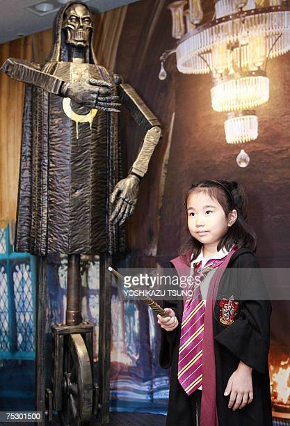 Young Harry Potter fan Moka Suzuki poses next to a property of Harry Potter movie as she visits a preview of Harry Potter exhibition which displays...