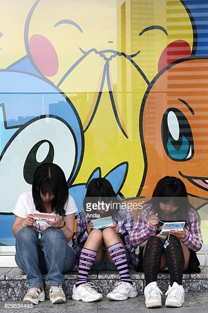 Tokyo May 2010 Japanese people and video games Here in front of the offical Pokemon store three teenage girls playing the Nintendo DS seated on the...