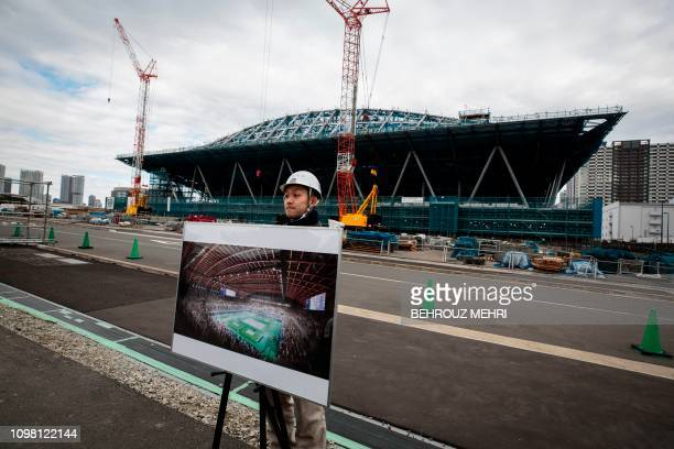A Tokyo Metropolitan Government employee displays a computer generated indoor image at the under construction Ariake Gymnastics Centre venue for the...
