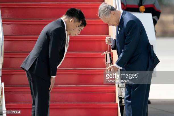 Tokyo Olympic and Paralympic Organizing Committee President Yoshiro Mori bows after receiving the Olympic flame from Olympic gold medalists Tadahiro...
