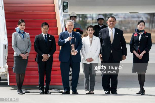 Tokyo Olympic and Paralympic Organizing Committee President Yoshiro Mori holding the Olympic flame walks to the podium with Olympic gold medalists...