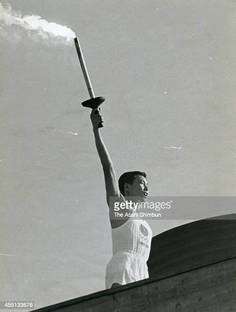 Tokyo Olympic final torch runner Yoshinori Sakai lights the Olympic cauldron during the opening ceremony of the 1964 Tokyo Olympics at the national...