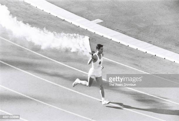 Tokyo Olympic final torch runner Yoshinori Sakai runs during the opening ceremony of the 1964 Tokyo Olympics at the national stadium on October 10...