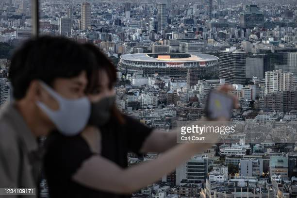 Tokyo Olympic Stadium is pictured in the background as a couple take a selfie photograph on Shibuya Sky Deck on July 22, 2021 in Tokyo, Japan....