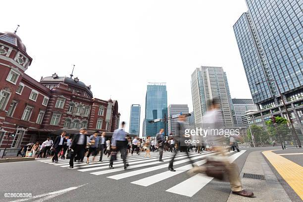 tokyo railroad station behind busy city commuters - tokyo station stock photos and pictures