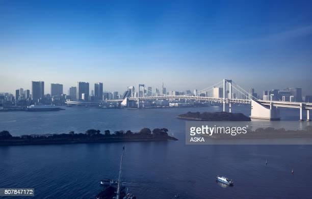 Tokyo Rainbow Bridge soaring over harbour bay futuristic cityscape Japan