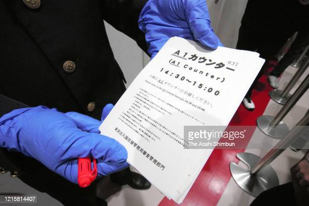 Tokyo Regional Immigration Bureau staff wearing rubber gloves distributes numbered ticket to foreign citizens who wish to extend their visas as they...