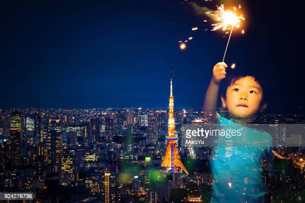 Tokyo Skyline at Night with boy playing fireworks