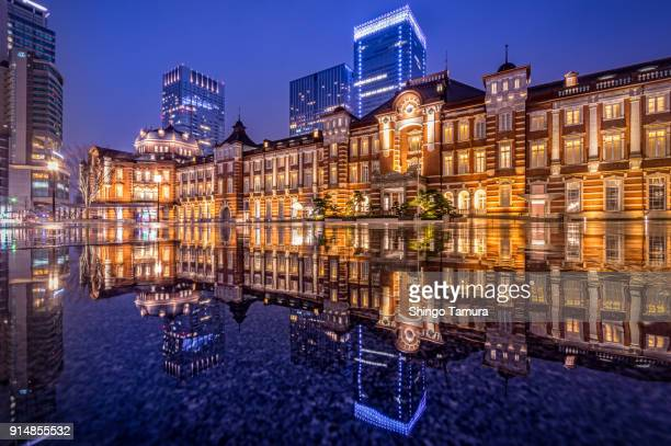 tokyo station with reflection by night - tokyo station stock photos and pictures