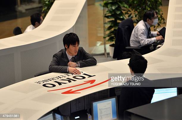 Tokyo Stock Exchange employees operate computers for trading at the TSE in Tokyo on March 19 2014 Panel maker Japan Display shares plunged from their...