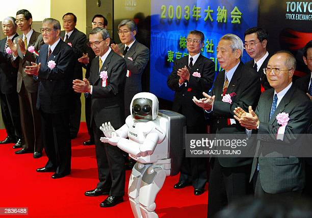 Tokyo Stock Exchange executives and Honda's humanoid robot Asimo clap their hands to celebrate the closing on the last trading of this year at the...