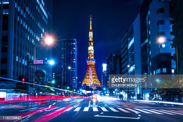 tokyo tower spotlit dusk overlooking zooming traffic city streets japan - tokyo japan stock pictures, royalty-free photos & images