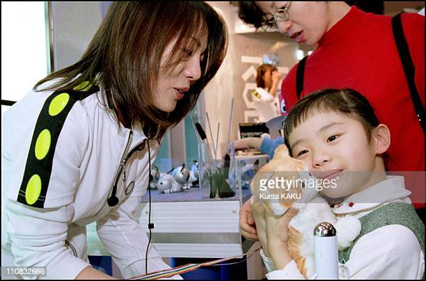 Tokyo Toy Show In Tokyo Japan On March 19 2000 Little girl hug a cat robot mew when you pat the head cat wag his tail you touch a face cat mew