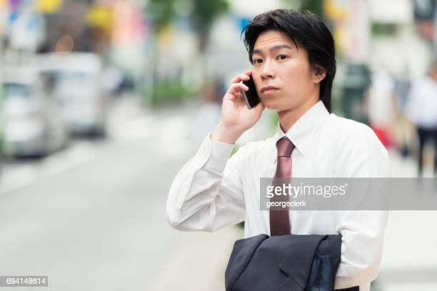tokyo - young businessman on the phone - wages stock photos and pictures