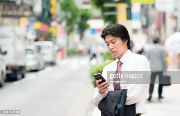 東京の青年実業家のスマート フォンを使用して