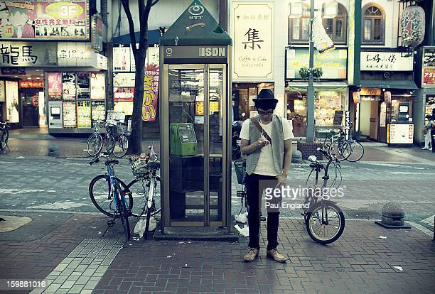 Tokyoite checks his smart phone in front of an ISDNequipped phone booth