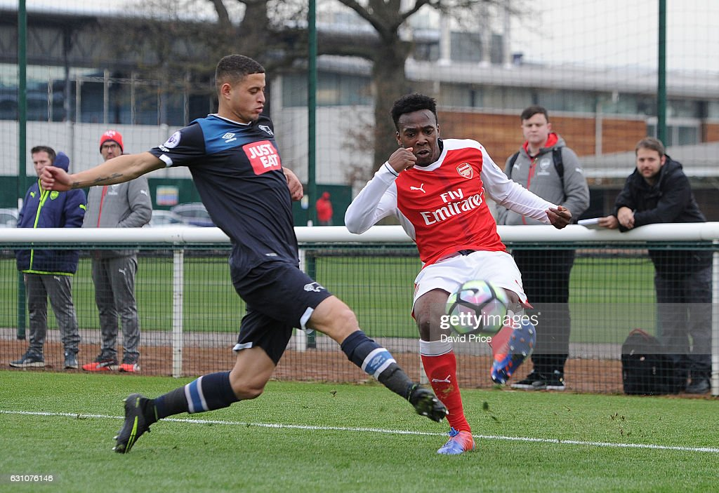 Tolaji Bola of Arsenal crosses under pressure from Alefe Santos of Derby during the match between Arsenal U23 and Derby County U23 at London Colney on January 6, 2017 in St Albans, England.