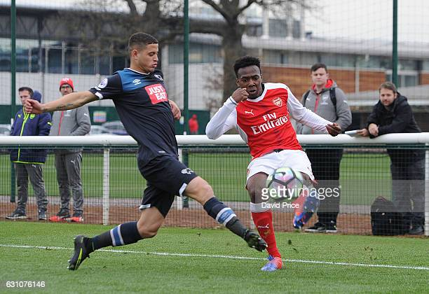 Tolaji Bola of Arsenal crosses under pressure from Alefe Santos of Derby during the match between Arsenal U23 and Derby County U23 at London Colney...