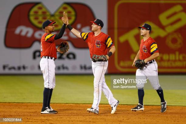 Toledo Mud Hens right fielder Mike Gerber slaps hands with shortstop Dixon Machado while left fielder Jacob Robson looks on at the conclusion of a...