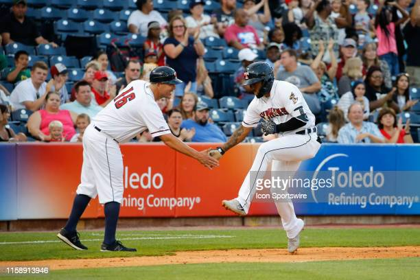 Toledo Mud Hens second baseman Ronny Rodriguez is congratulated by Toledo Mud Hens manager Doug Mientkiewicz as he rounds third base after hitting a...