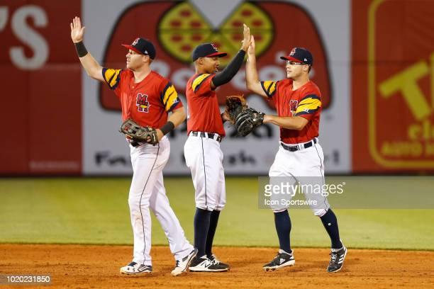 Toledo Mud Hens shortstop Dixon Machado congratulates right fielder Mike Gerber and left fielder Jacob Robson at the conclusion of a regular season...