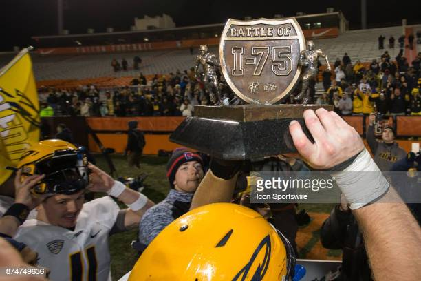 Toledo player holds the Battle of I75 trophy up at the conclusion of the game between the Toledo Rockets and the Bowling Green Falcons on November 15...