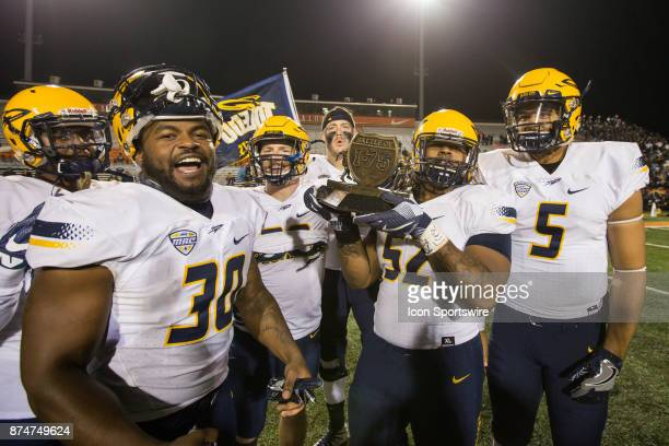 Toledo players hold the Battle of I75 trophy at the conclusion of the game between the Toledo Rockets and the Bowling Green Falcons on November 15...