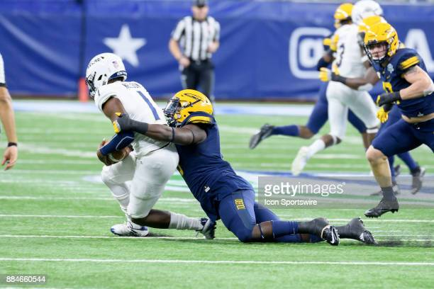 Toledo Rockets DE Olasunkanmi Adeniyi tackles Akron Zips QB Kato Nelson in the first quarter of 3the MAC Championship game between Akron Zips and...