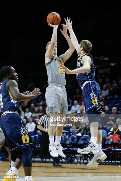 Toledo Rockets guard Jaelan Sanford shoots over Kent State Golden Flashes guard Mitch Peterson during a regular season basketball game between the...