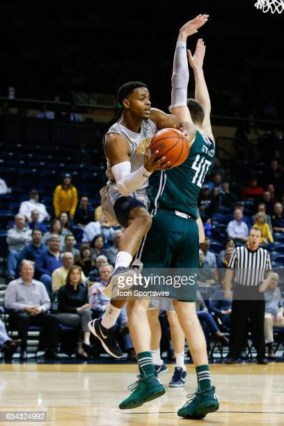 Toledo Rockets guard Jonathan Williams looks to pass the ball against Eastern Michigan Eagles center Baylee Steele during a regular season basketball...