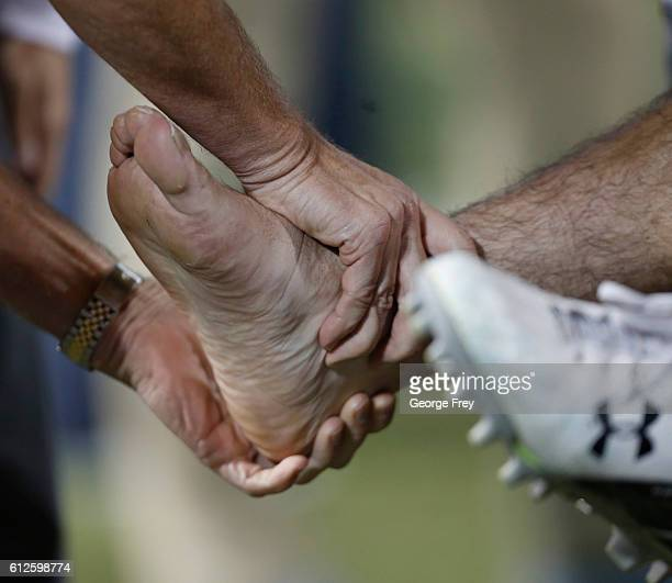 Toledo Rockets players has his ankle look at by a trainer during the first half at a college football game against the Brigham Young Cougars at...
