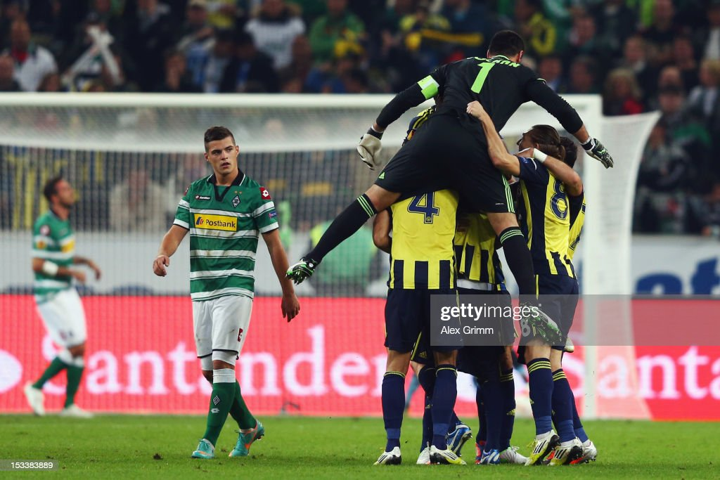 Tolga Cigerci (L) reacts as Raul Mereiles of Fenerbahce celebrates his team's second goal with team mates during the UEFA Europa League group C match between Borussia Moenchengladbach and Fenerbahce SK at Borussia-Park on October 4, 2012 in Moenchengladbach, Germany.