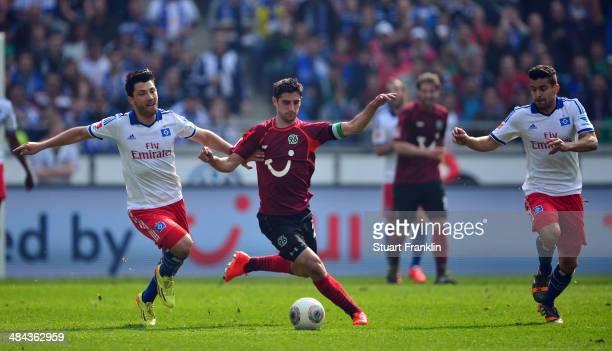 Tolgay Arslan of Hamburg is challenged by Lars Stindl of Hannover during the Bundesliga match between Hannover 96 and Hamburger SV at HDI-Arena on...