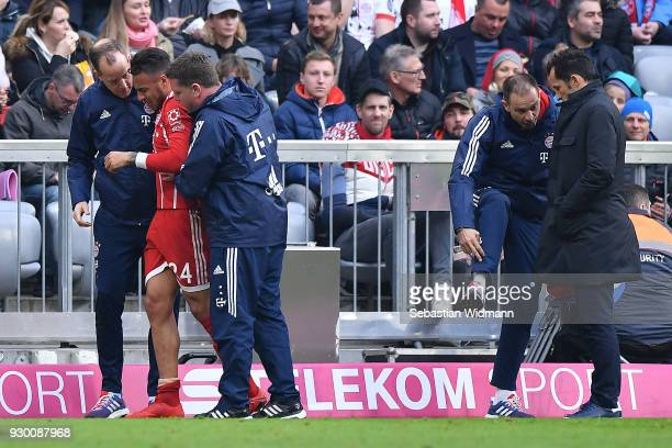 Tolisso of Bayern Muenchen is escorted off the pitch due to injury while Hasan Salihamidzic sporting director of Bayern Muenchen listens to the medic...