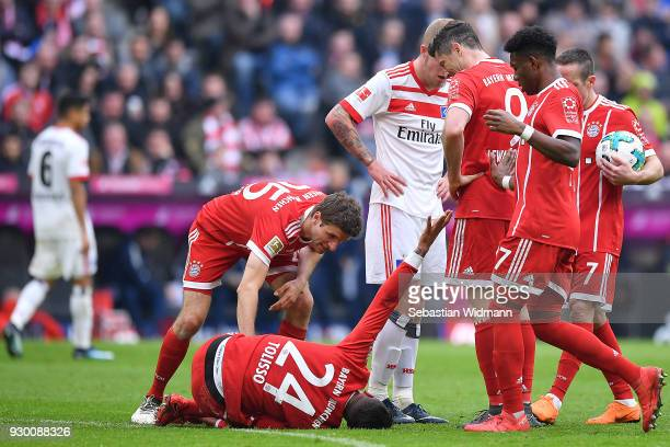 Tolisso of Bayern Muenchen lies on the pitch in pain as players gather around him during the Bundesliga match between FC Bayern Muenchen and...