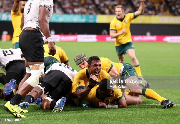 Tolu Latu of Australia is congratulated by his team mates after scoring his side third try during the Rugby World Cup 2019 Group D game between...