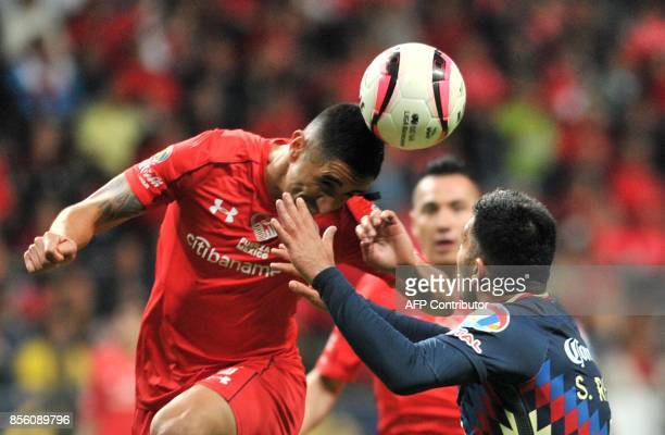 Toluca's defender Osvaldo Gonzalez vies for the ball with America's forward Silvio Romero during their Mexican Apertura tournament football match at...