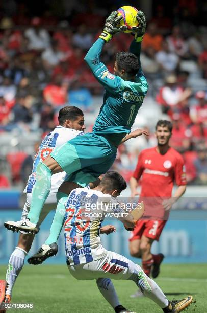 Toluca's goalie Alfredo Talavera jumps to grab the ball between Pachuca's Franco Jara and Alexis Pena during their Mexican Clausura tournament...