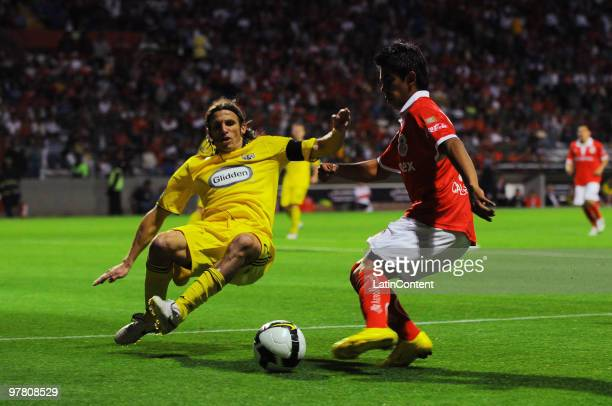 Toluca's player Nestor Calderon vies for the ball with Frankie Hejduk of Columbus during their match as part of the 2010 Concachampions Tournament at...