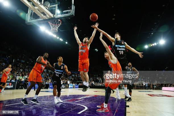Tom Abercrombie of the Breakers competes for a rebound against Mitch McCarron and Cameron Gliddon of the Taipans during the round 13 NBL match...