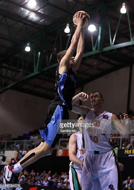 Tom Abercrombie of the Breakers stretches over Russell Hinder of the Crocs during the round 21 NBL match between the New Zealand Breakers and the...