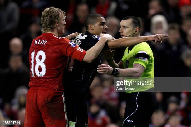 Tom Adeyemi of Oldham Athletic is restrained by Dirk Kuyt of Liverpool after being abused by fans on the Kop during the FA Cup 3rd Round match...