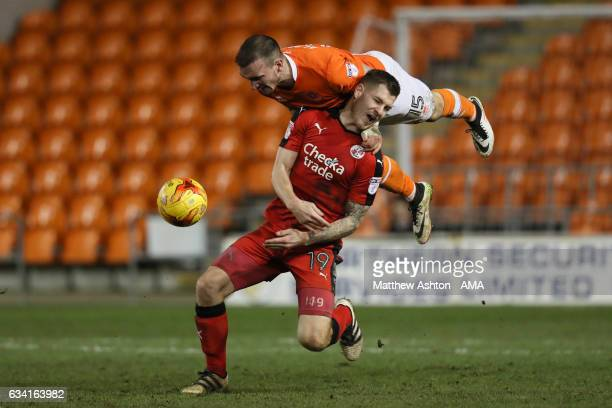 Tom Aldred of Blackpool heads the ball away from James Collins of Crawley Town during the Sky Bet League Two match between Blackpool and Crawley Town...