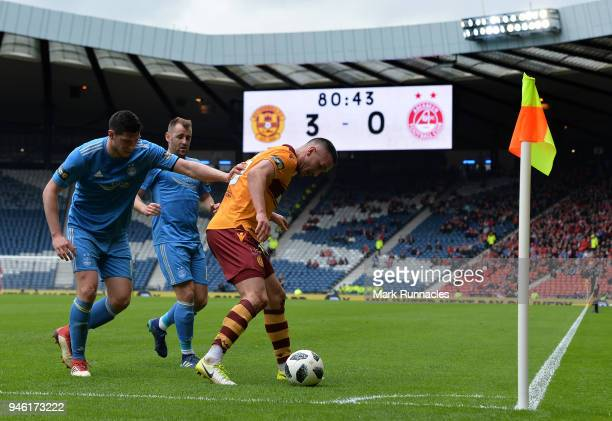 Tom Aldred of Motherwell shields the ball from Scott McKenna and Niall McGinn of Aberdeen during the Scottish Cup Semi Final match between Motherwell...