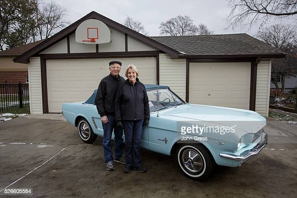 Tom and Gail Wise pose with Gail's Skylight Blue 1964 1/2 Ford Mustang convertible outside their garage where it sat for 27 years before its...