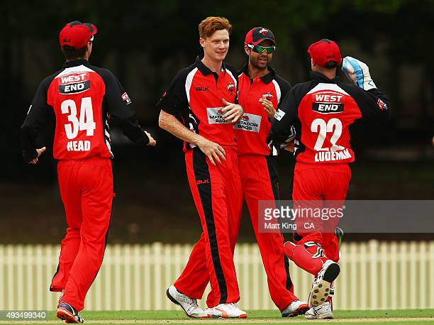 Tom Andrews of the Redbacks celebrates with team mates after taking the wicket of James Peirson of Cricket Australia XI during the Matador BBQs One...